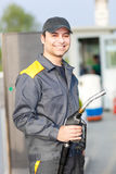Smiling gas station worker holding a fuel nozzle Royalty Free Stock Images
