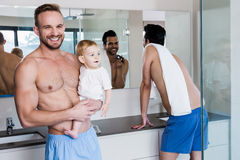 Smiling gay couple with child. In the bathroom Royalty Free Stock Image