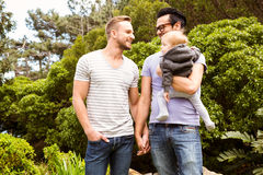 Smiling gay couple with child. In garden Royalty Free Stock Photo