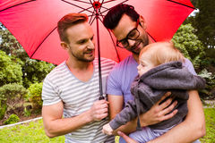 Smiling gay couple with child. In garden Royalty Free Stock Images