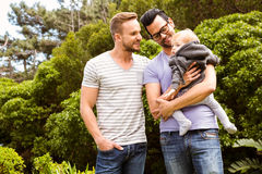 Smiling gay couple with child stock images
