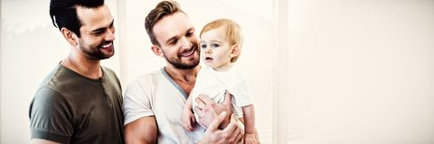 Gay couple with child at home royalty free stock image