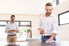 Smiling gay couple cleaning living room. At home stock photography