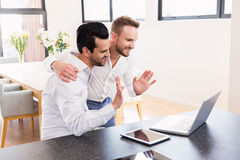 Smiling gay couple doing video chat Stock Image