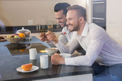 Smiling gay couple having breakfast Stock Photo