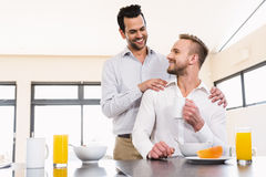 Smiling gay couple having breakfast Royalty Free Stock Photography