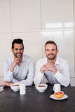Smiling gay couple having breakfast Stock Photography