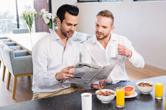 Smiling gay couple reading newspaper Royalty Free Stock Images