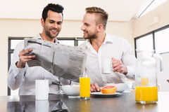 Smiling gay couple reading newspaper Royalty Free Stock Image