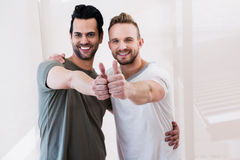 Smiling gay couple showing thumbs up. At home Stock Photo