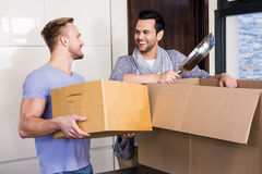 Smiling gay couple unpacking cardboard Stock Images