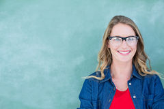 Smiling geeky teacher standing in front of blackboard. In classroom Stock Photos