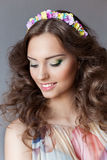 Smiling gentle elegant young beautiful girl with lush hair with a rim of bright colors Royalty Free Stock Image