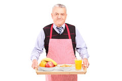 A smiling gentleman in apron carrying a tray with drinks and food Stock Photography