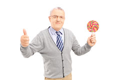 Smiling gentleman holding a colorful lollipop and giving thumb u Royalty Free Stock Images