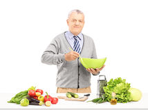 Smiling gentleman prepairing meal with fresh vegetables Stock Photography
