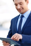 Smiling gentleman in the process of using a tablet Royalty Free Stock Images