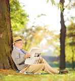 Smiling gentleman seated reading a newspaper in a park at autumn. Smiling senior gentleman seated on a grass reading a newspaper in a park at autumn, shot with a Royalty Free Stock Photo
