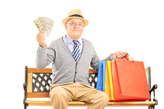 Smiling gentleman sitting on a bench with bags and holding money Stock Photography