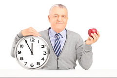Smiling gentleman sitting and holding a wall clock and an apple Royalty Free Stock Images