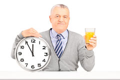 Smiling gentleman sitting and holding a wall clock and glass of Royalty Free Stock Images
