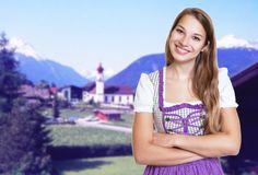 Smiling german woman in bavarian dirndl with rural landscape. In the background royalty free stock photo