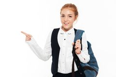 Smiling gigner student woman with backpack pointing away Royalty Free Stock Photography