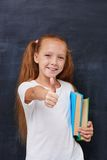 Smiling ginger girl with books and showing thumbs Royalty Free Stock Images