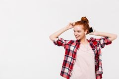 Smiling ginger woman in shirt and headphones listening music royalty free stock photography