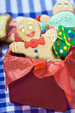 Smiling gingerbread man cookies. And the rest in a gift box Stock Photo