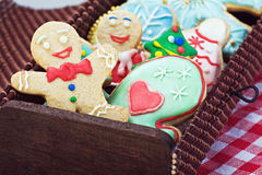 Smiling gingerbread man cookies and the rest in a gift box. Focus on the first cookie Royalty Free Stock Image