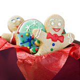 Smiling gingerbread man cookies and the rest in a gift box. On a white background. Focus on the first cookie Royalty Free Stock Photo