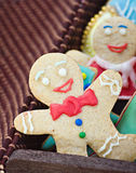 Smiling gingerbread man cookies. And the rest in a gift box on a white background. Focus on the first cookie Royalty Free Stock Photo