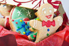 Smiling gingerbread man cookies and the rest in a gift box. On a white background. Focus on the first cookie Royalty Free Stock Photography
