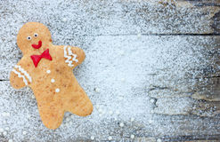 Smiling gingerbread man on wooden background Stock Photography
