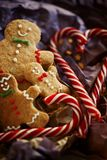 Smiling gingerbread man on wrapping paper with candy cane close-up. Christmas cookies on a dark background. Christmas gift stock image
