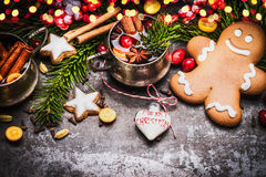 Smiling gingerbread men with mug of mulled wine , Christmas decoration and holiday cookies and spices on dark rustic background wi. Th festive bokeh lighting Royalty Free Stock Image