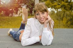 Smiling gir lies on the road stock images
