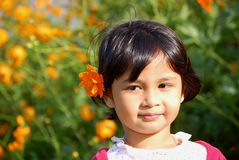 Smiling Girl. Portrait of an asian girl smiling with cosmos at ear Royalty Free Stock Images