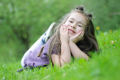 Smiling girl. On the grass in park Royalty Free Stock Images