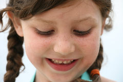Smiling girl. An adorable little girl with freckles and pigtails smiles while looking down Royalty Free Stock Photos