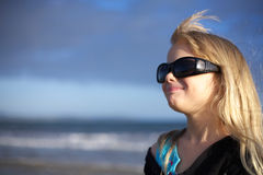 Smiling girl. A cute little blond girl looking cool in black sunglasses royalty free stock photos