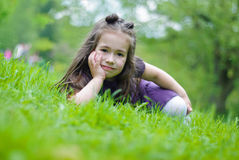 Smiling girl. On the grass in park Royalty Free Stock Image