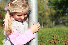 Smiling girl. Little girl that is smiling by a column royalty free stock photos