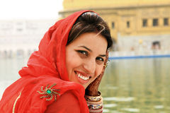 Smiling girl. Smiling indian girl sitting in front of golden temple royalty free stock photo