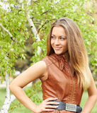 Smiling girl. In a brown vest near a birch Royalty Free Stock Images