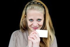 Smiling girl. Holding a white paper in her hand Royalty Free Stock Photos