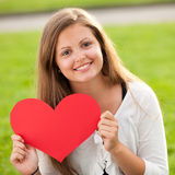Smiling girl. Happy young girl holding red heart on Valentine's Day Stock Photos