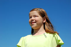 Smiling Girl. A girl smiling in the wind.  A girl smiling with the blue sky as the backdrop Stock Photography