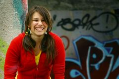 Smiling girl. Young teenager with a big smile with a graffiti wall in background Royalty Free Stock Photo